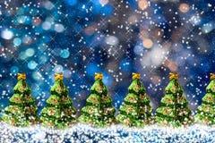 Rangée des arbres de Noël verts en verre de jouet sur le fond du bokeh bleu avec l'espace de neige et de copie Photos stock