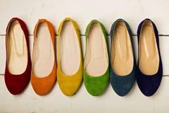 Rangée des ballerines colorées de chaussures sur un fond en bois blanc Photos libres de droits