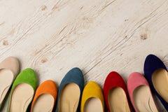 Rangée des ballerines colorées de chaussures sur un fond en bois blanc Images stock