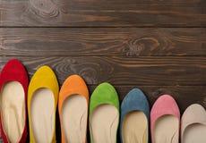 Rangée des ballerines colorées de chaussures sur un fond en bois foncé Photo stock