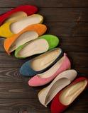 Rangée des ballerines colorées de chaussures sur un fond en bois foncé Image libre de droits
