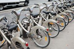 Rangée des bicyclettes publiques de ville grise pour le loyer Photos libres de droits