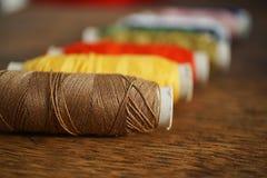 Rangée des bobines colorées avec les fils jaunes, bruns, verts, de rouge et de bleu Images stock