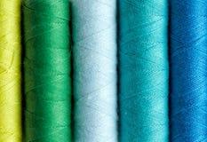 Rangée des bobines colorées de fil sur la table Photos libres de droits