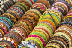 Rangée des bracelets colorés de fil sur le marché de bijoux Photographie stock libre de droits