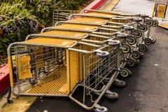Rangée des caddies inclinés plus de dans le parking Photos stock