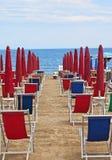 Rangée des canapés et des parasols vides du soleil Photos stock