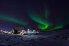 Rangée des carlingues et des lumières du nord vertes dans la banlieue de Nuuk Photos libres de droits