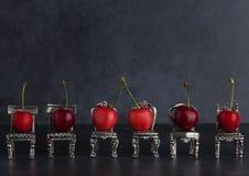 Rangée des cerises red delicious placées sur des chaises d'argent de vintage dessus Photos stock