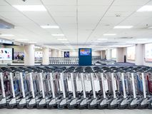 Rangée des chariots de bagage d'aéroport dans le terminal d'aéroport image stock