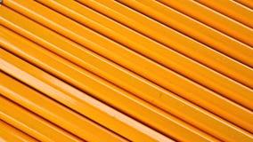 Rangée des crayons affilés identiques avec le revêtement orange Concept d'égalité, chariot banque de vidéos