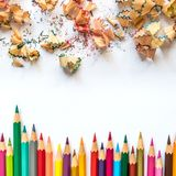 Rangée des crayons colorés et des rasages de crayon sur un papier images stock