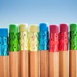 Rangée des crayons de couleur sur le fond bleu studio Images stock
