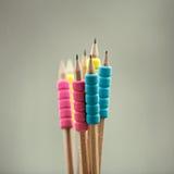 Rangée des crayons de couleur sur le fond gris studio Photos stock