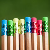 Rangée des crayons de couleur sur le fond vert studio Images stock