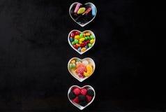 Rangée des cuvettes en forme de coeur en céramique sur le noir Images libres de droits