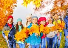 Rangée des enfants heureux avec des groupes de râteau et de feuilles Image stock