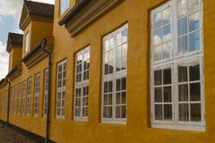 Rangée des fenêtres de tissu pour rideaux sur la maison jaune Images libres de droits