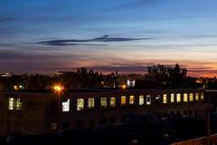 Rangée des fenêtres lumineuses dans l'information principale du vieux bâtiment industriel au lever de soleil images stock