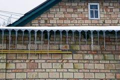 Rangée des glaçons d'un toit sur un mur de briques à la maison Image stock