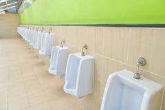 Rangée des hommes extérieurs d'urinoirs Image libre de droits