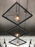 Rangée des lampes accrochantes modernes nues sous le plafond de ciment Image stock