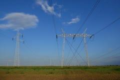 Rangée des lignes de transmission contre le ciel bleu Photographie stock