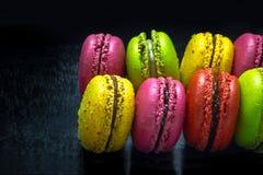 Rangée des macarons colorés français sur le fond noir Photos stock