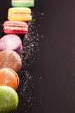 Rangée des macarons sur le noir Photographie stock libre de droits