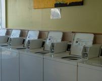 Rangée des machines à jetons de blanchisserie de blanchisserie à l'intérieur d'un laundroma photos stock