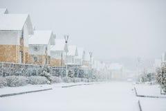 Rangée des maisons bloquées par la neige, maisons avec le trottoir sur le St vide photos libres de droits