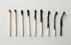 Rangée des matchs et de la totalité brûlés un sur le backgroundncept léger photos libres de droits