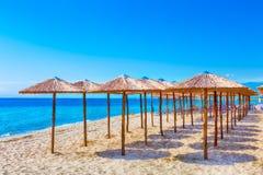 Rangée des parapluies en bois à la plage sablonneuse, mer Photographie stock libre de droits