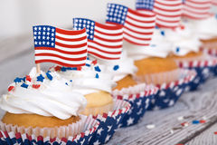 Rangée des petits gâteaux patriotiques avec les drapeaux américains Photographie stock libre de droits