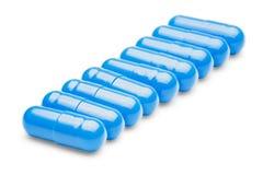 Rangée des pilules médicales bleues sur le fond blanc d'isolement Photographie stock libre de droits