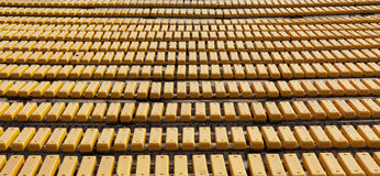 Rangée des sièges en bois jaunes sur une photo spectaculaire de tribune Photographie stock