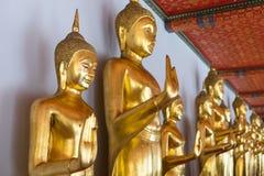 Rangée des statues de Bouddha chez Wat Pho ce temple célèbre à Bangkok Photographie stock libre de droits