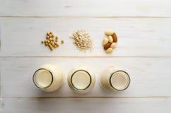 Rangée des substituts de lait mis en bouteille avec des ingrédients sur le bois blanc P Images libres de droits