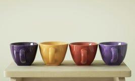 Rangée des tasses colorées sur la table Image libre de droits