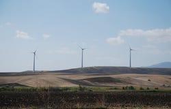 Rangée des turbines de vent, Puglia Photographie stock