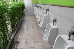 Rangée des urinoirs blancs extérieurs de toilette publique d'hommes d'urinoir dans la salle de bains des hommes Images libres de droits