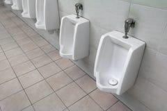 Rangée des urinoirs blancs extérieurs de toilette publique d'hommes d'urinoir dans la salle de bains des hommes Photo libre de droits