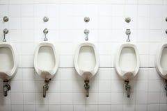 Rangée des urinoirs dans la toilette Images libres de droits