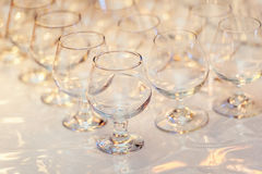 Rangée des verres vides de cognac sur la table Images stock
