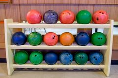 Rangée multi de couleur de boule de bowling sur le support en bois image stock