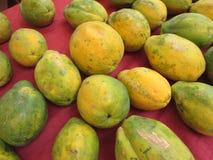 Rangées de grandes papayes hawaïennes de déchirure sur le tissu rouge Photographie stock libre de droits