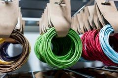 Rangées de la corde de papier multicolore accrochant sur le support pour le stor en gros Photographie stock libre de droits