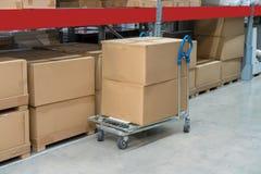 Rangées des étagères avec des boîtes et des chariots de stockage dans l'entrepôt images stock