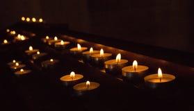 Rangées des bougies rougeoyantes dans l'obscurité Bougies avec le falme brûlant Décoration d'église Fond de religion et de foi images stock
