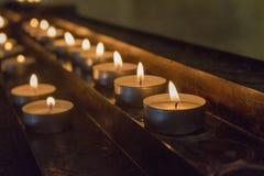Rangées des bougies rougeoyantes dans l'obscurité Bougies avec le falme brûlant Décoration d'église Fond de religion et de foi photos libres de droits